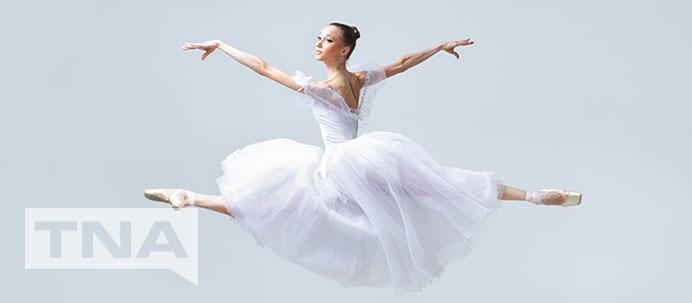 Ballerina leaping through the air in white tutu