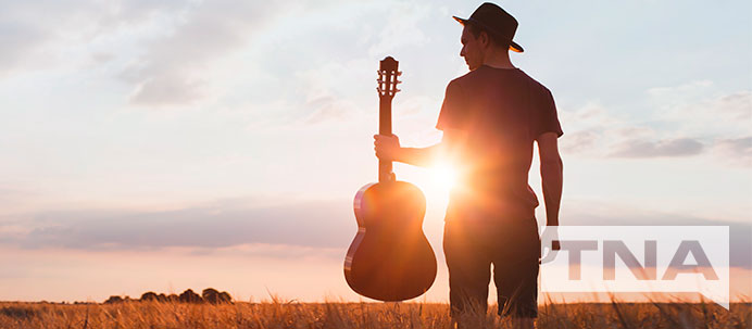 Man holding a guitar in a field against a sunset