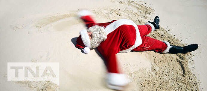 Santa making a snow angel in the sand at a beach