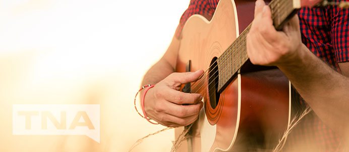Country musician playing guitar in a sunny field