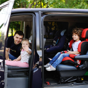 Father and his kids in a mini van ready for a holiday