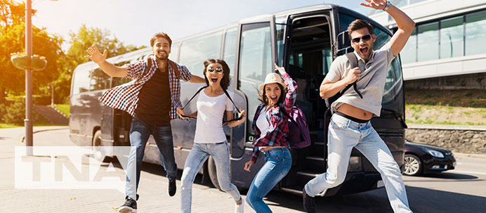 Jumping for joy on holiday in front of a charter bus