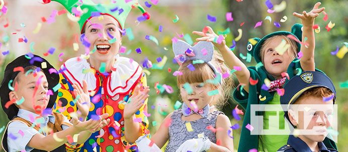 Kids in costume throwing confetti with a jester