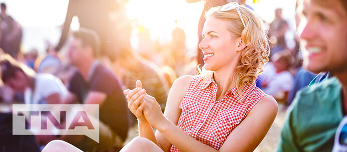 Caucasian woman clapping to music whilst sitting on the grass in the sun