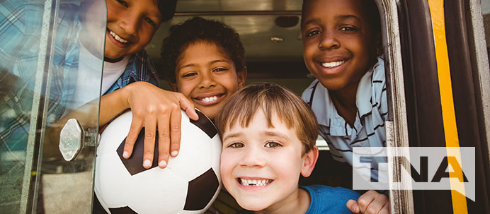 Smiling kids from school soccer team on a charter bus