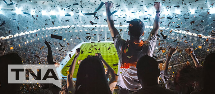 Sport fan cheering as confetti falls from the sports stadium roof