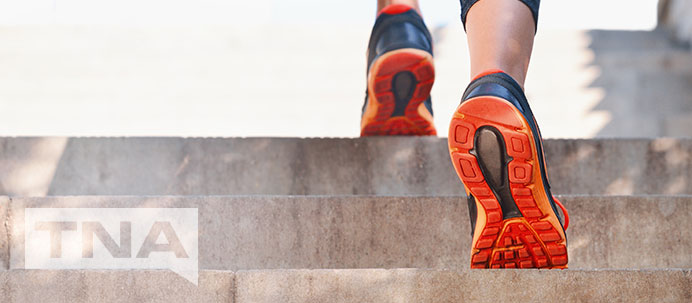 Running up stairs with orange sports shoes