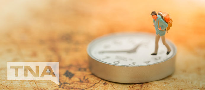 Tiny time traveller walking on a clock on a map